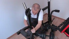 Trabajador con los componentes de la máquina del ejercicio metrajes