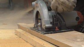 Trabajador con madera de los cortes de la sierra almacen de metraje de vídeo