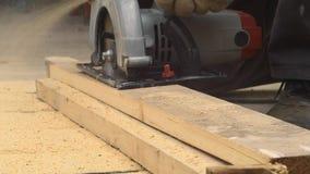 Trabajador con madera de los cortes de la sierra almacen de video