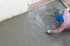 Trabajador concreto del cemento del yesero que enyesa el suelo Fotos de archivo