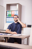 Trabajador corporativo sonriente en camisa azul y lazo que hablan en el pH Imágenes de archivo libres de regalías