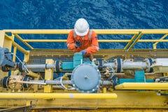 Trabajador costero de la plataforma petrolera que comprueba el parámetro del metro digital del transmisor de flujo de los corioli imagenes de archivo