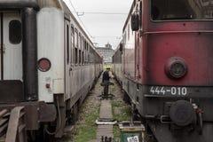 Trabajador de carril manoevring entre dos trenes de pasajeros en las plataformas de la estación de tren de Belgrado, haciéndolas  imagen de archivo libre de regalías