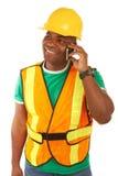 Trabajador de construcción afroamericano feliz en el teléfono móvil imágenes de archivo libres de regalías