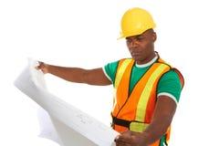 Trabajador de construcción afroamericano serio que sostiene modelos imagen de archivo libre de regalías