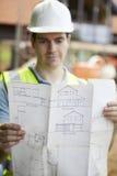 Trabajador de construcción On Building Site que mira planes de la casa Imagen de archivo libre de regalías