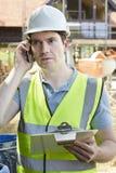 Trabajador de construcción On Building Site que usa el teléfono móvil Fotos de archivo