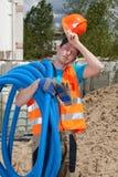 Trabajador de construcción cansado que sostiene los tubos fotos de archivo