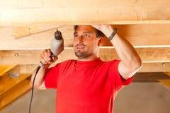 Trabajador de construcción con el taladro de mano Imágenes de archivo libres de regalías