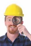 Trabajador de construcción con la lupa Foto de archivo libre de regalías