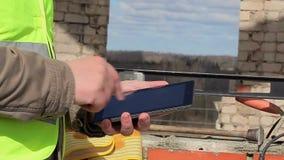 Trabajador de construcción con la tableta en el edificio inacabado metrajes