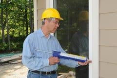 Trabajador de construcción con un calafateo Foto de archivo