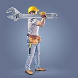 Trabajador de construcción con una correa de la herramienta y una llave Imagen de archivo