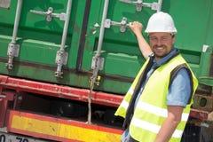 Trabajador de construcción de carreteras que se coloca al lado del camión en sitio de la ubicación Imágenes de archivo libres de regalías