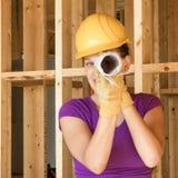 Trabajador de construcción de la mujer que mira a través del rollo de dibujos Foto de archivo