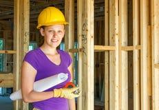 Trabajador de construcción de la mujer que sostiene dibujos arquitectónicos Foto de archivo libre de regalías