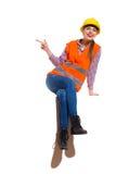 Trabajador de construcción de sexo femenino de risa Sitting And Pointing Foto de archivo libre de regalías
