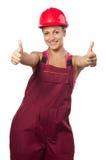 Trabajador de construcción de sexo femenino feliz que muestra los pulgares para arriba foto de archivo