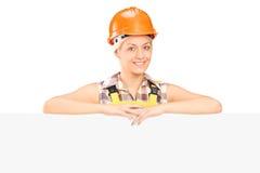 Trabajador de construcción de sexo femenino que presenta detrás del panel Fotos de archivo libres de regalías