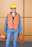 Trabajador de construcción de sexo femenino que presenta en sombrero duro Foto de archivo libre de regalías