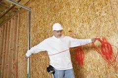 Trabajador de construcción de sexo masculino maduro con un alambre eléctrico Imágenes de archivo libres de regalías
