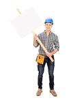 Trabajador de construcción de sexo masculino que lleva a cabo una muestra en blanco Foto de archivo
