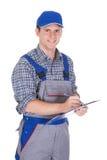 Trabajador de construcción de sexo masculino que sostiene el tablero Imagen de archivo libre de regalías