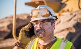 Trabajador de construcción en el teléfono celular Imagen de archivo libre de regalías