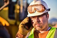 Trabajador de construcción en el teléfono celular Fotografía de archivo libre de regalías