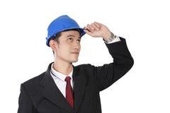 Trabajador de construcción en el traje que mira para arriba, aislado en blanco Imagen de archivo libre de regalías