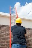 Trabajador de construcción en escala Imagen de archivo