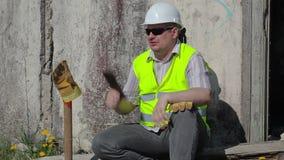 Trabajador de construcción enojado con la tableta cerca de la pared almacen de metraje de vídeo