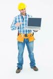 Trabajador de construcción feliz que señala en el ordenador portátil fotografía de archivo
