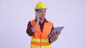 Trabajador de construcción hispánico feliz joven del hombre usando el teléfono y la tableta digital almacen de metraje de vídeo