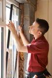 Trabajador de construcción Installing New Windows en casa Imágenes de archivo libres de regalías