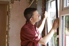 Trabajador de construcción Installing New Windows en casa Foto de archivo libre de regalías