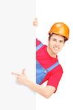 Trabajador de construcción joven con el casco que gesticula en un panel en blanco Foto de archivo libre de regalías