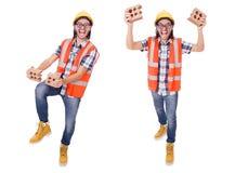 Trabajador de construcción joven divertido con el ladrillo quebrado aislado en wh imagen de archivo