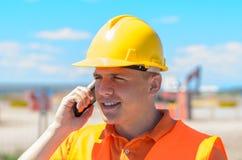 Trabajador de construcción joven que habla en un móvil Imágenes de archivo libres de regalías