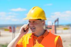 Trabajador de construcción joven que habla en un móvil Fotografía de archivo