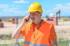 Trabajador de construcción joven que habla en un móvil Fotos de archivo libres de regalías
