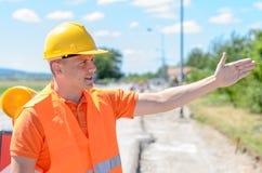 Trabajador de construcción joven que señala con su mano Foto de archivo libre de regalías