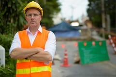 Trabajador de construcción maduro del hombre en el emplazamiento de la obra en la c Foto de archivo