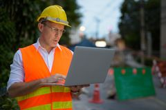 Trabajador de construcción maduro del hombre en el emplazamiento de la obra en la c Imagenes de archivo