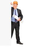 Trabajador de construcción maduro que se coloca detrás del panel Imagen de archivo libre de regalías