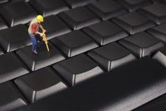 Trabajador de construcción miniatura On Top Of un teclado de ordenador fotos de archivo libres de regalías