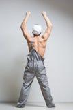 Trabajador de construcción muscular en guardapolvos imagen de archivo