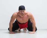 Trabajador de construcción muscular en guardapolvos Arrodillamiento imagenes de archivo