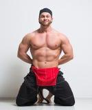 Trabajador de construcción muscular en guardapolvos Arrodillamiento foto de archivo libre de regalías