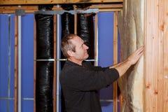 Trabajador de construcción que aísla termalmente el ático de la casa con las lanas de cristal Imagen de archivo
